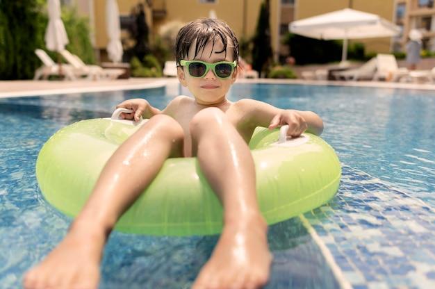 Close-upjongen in vlotter bij pool Premium Foto