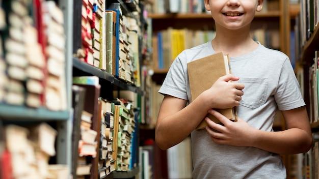 Close-upjongen tussen boekenrekken Gratis Foto