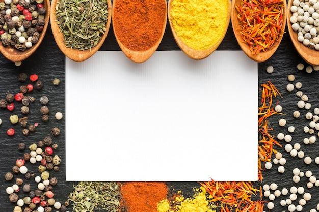 Close-uplepels met kruidenpoeder en specerijen op lijst worden uitgespreid die Gratis Foto