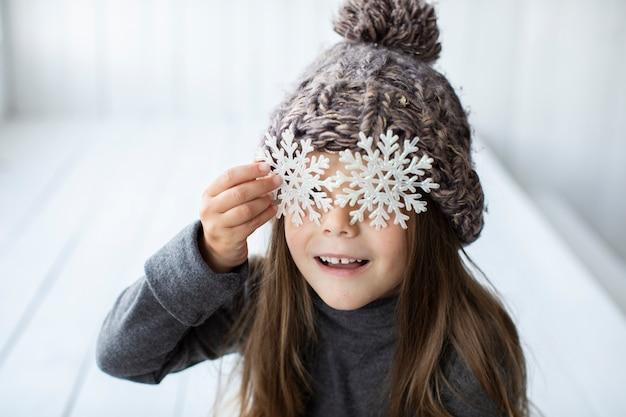 Close-upmeisje die haar gezicht behandelen met sneeuwvlokken Gratis Foto