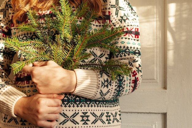 Close-upmeisje met leuke sweater en sparrentakjes Gratis Foto