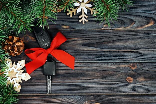 Close-upmening van autosleutels met rode boog zoals huidig op houten uitstekende achtergrond Premium Foto