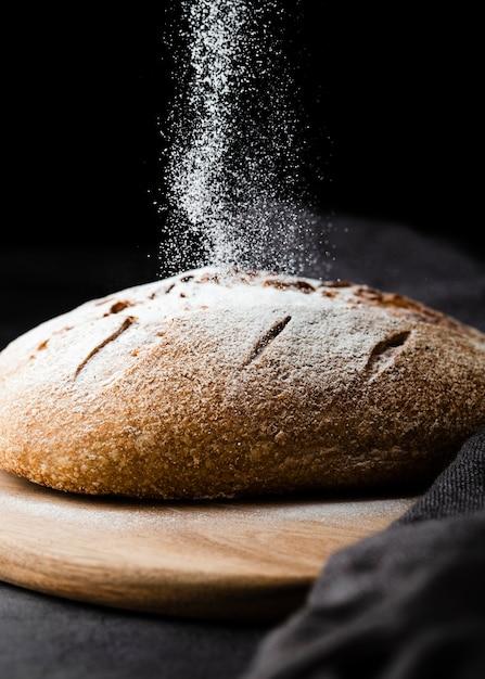 Close-upmening van brood op bijl met zwarte achtergrond Gratis Foto