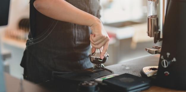 Close-upmening van de malende koffie van de vrouwelijke barista-hand met molenmachine Premium Foto