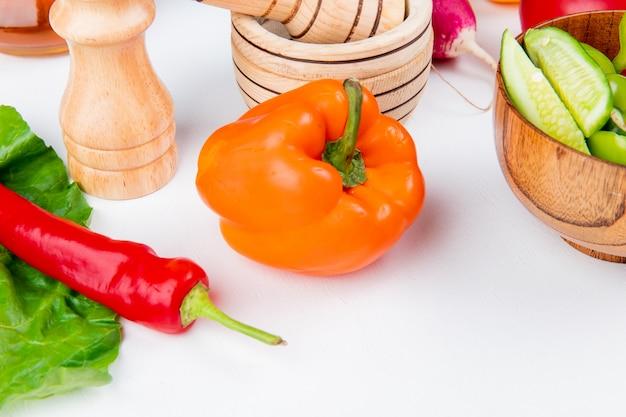 Close-upmening van groenten als radijs van de pepertomaat met plantaardige salade zoute zwarte peper en verlof op witte lijst Gratis Foto