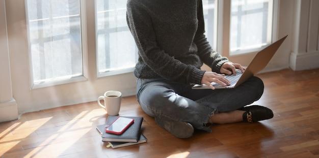 Close-upmening van het jonge vrouwelijke freelancer typen op laptop computer terwijl het zitten naast de vensters Premium Foto