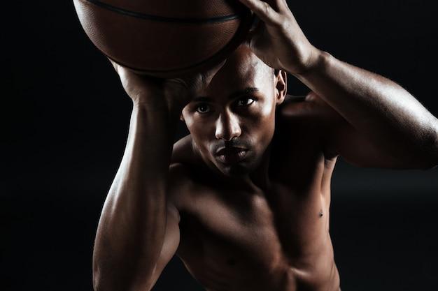 Close-upmening van jonge afro-amerikaanse basketbalspeler die bal voorbereidingen treft te werpen Gratis Foto