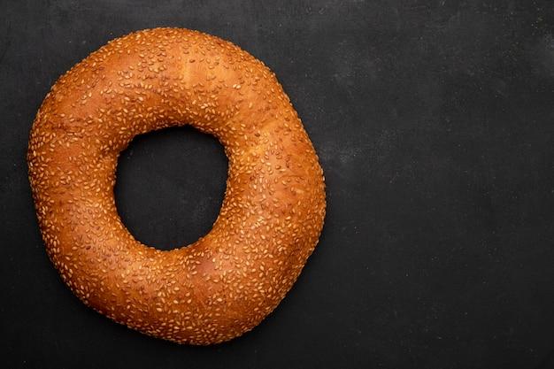 Close-upmening van turks sesamongezuurde broodje aan linkerkant en zwarte achtergrond met exemplaarruimte Gratis Foto