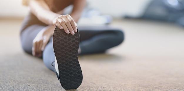 Close-upmening van vrouw met tan en slanke lichaam het uitrekken zich benen vóór oefening Premium Foto