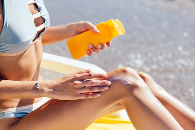 Close-upmening van vrouwelijke handen die zonnescherm op haar been, op het strand toepassen. zonnen. Gratis Foto