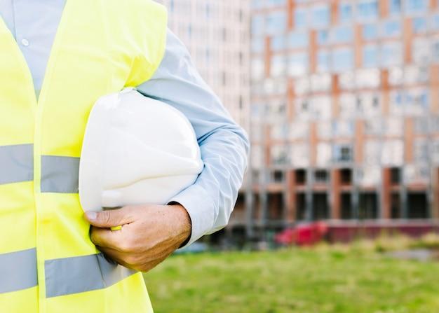 Close-upmens met vest die helm steunen Gratis Foto