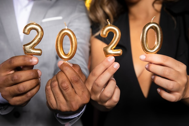 Close-upmensen die kaarsen met nieuw jaar 2020 houden Gratis Foto