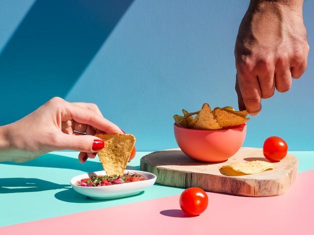 Close-upmensen met tortillaspaanders en saus Gratis Foto
