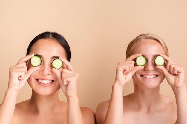 Close-upmodellen die met komkommerplakken stellen Gratis Foto