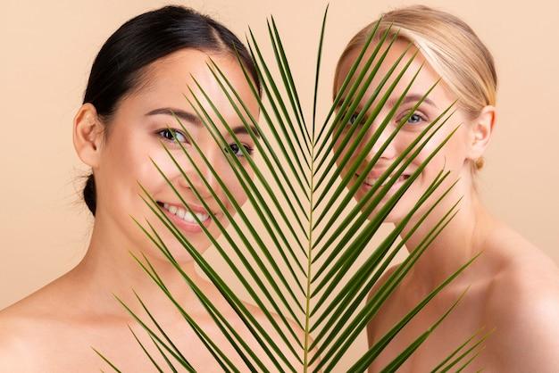 Close-upmodellen die samen met bladeren stellen Gratis Foto