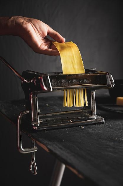 Close-uppersoon met pastamachine en deeg Gratis Foto