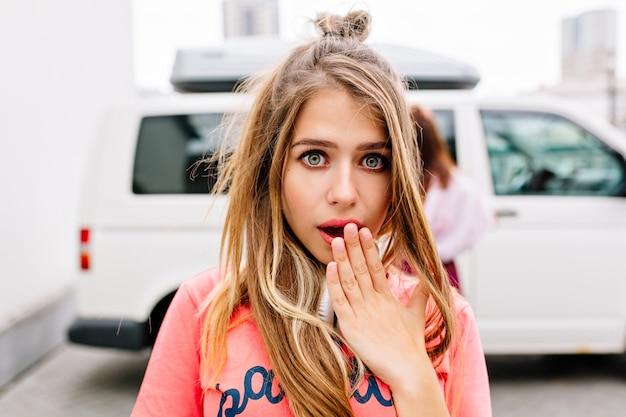 Close-upportret dat van geschokte jonge vrouw open mond behandelt met haar hand, die zich dichtbij witte auto bevindt Gratis Foto