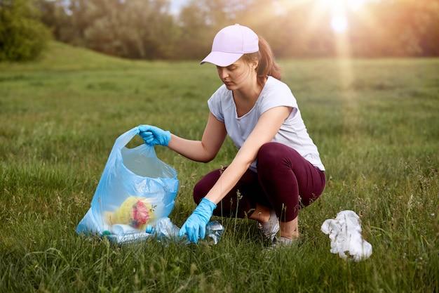 Close-upportret die van jonge vrouw t-shirt, broeken en honkbal glb dragen, vuilnis in weide opnemen aan vuilniszak, die op gebied tijdens zonsondergang stellen. Premium Foto