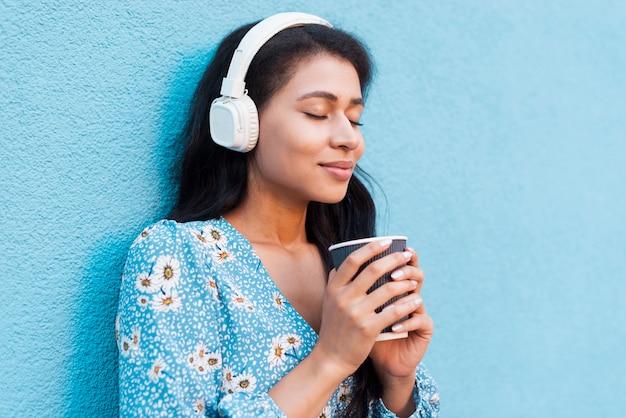 Close-upportret die van zijdelings vrouw een koffie houden Gratis Foto