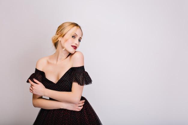 Close-upportret van aantrekkelijk blond meisje dat sensueel kijkt, zich goed voelt, poseren. ze heeft een mooie zachte huid en kapsel met krul. het dragen van zwarte jurk met open schouders. geïsoleerd. Gratis Foto