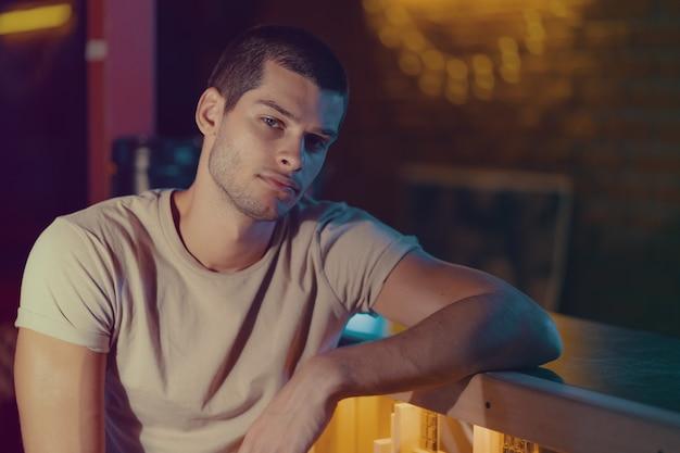 Close-upportret van aantrekkelijk mannelijk model. jonge knappe man in een bar Gratis Foto