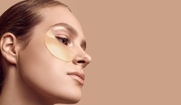 Close-upportret van aantrekkelijk sensueel meisje met naakte schouders die flarden op haar gezicht op studioachtergrond toepassen Gratis Foto