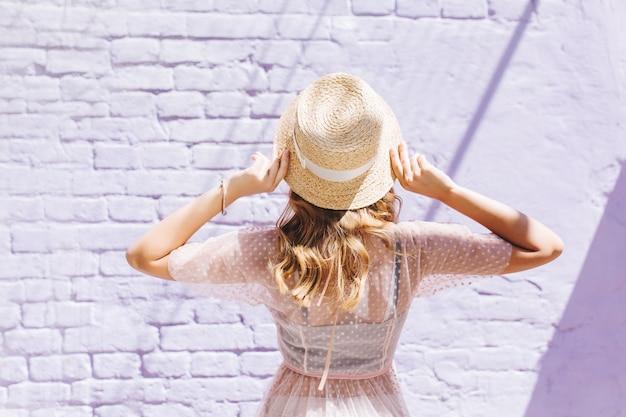 Close-upportret van achterkant van slank romantisch meisje in lichte kleding die oude muur bekijken Gratis Foto