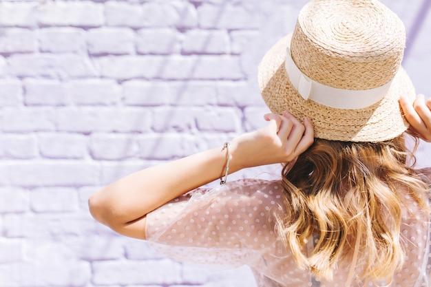 Close-upportret van blond meisje met licht gebruinde huid poseren met handen omhoog voor witte muur Gratis Foto