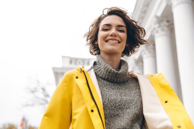 Close-upportret van charmante jonge vrouw die met loodjeskapsel van gang door de stad in gele laag genieten die op camera glimlachen Gratis Foto