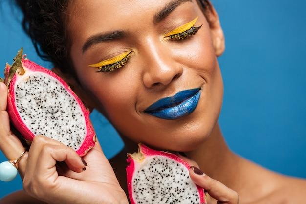 Close-upportret van de vrouw van tevreden afro met helder pitayafruit van de make-upholding die in de helft wordt genomen die genoegen met gesloten ogen, over blauwe muur nemen Gratis Foto