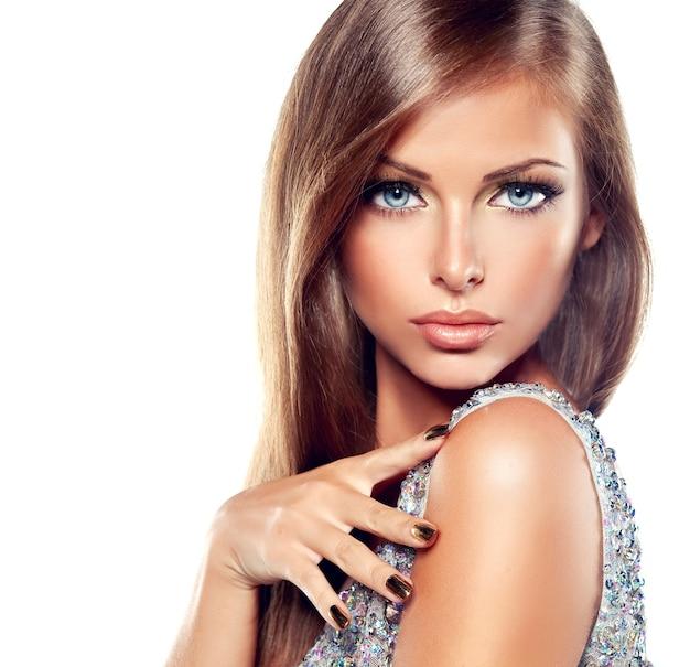 Close-upportret van een jonge vrouw in een chique avondmake-up, grote wimpers en vergulde nagellak Premium Foto