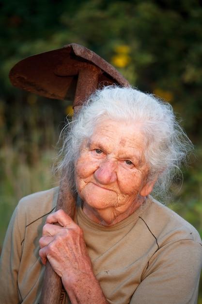 Close-upportret van een oude vrouw met grijs haar die en de camera glimlachen bekijken, een roestige schop in haar handen houden, gezicht in diepe rimpels Premium Foto