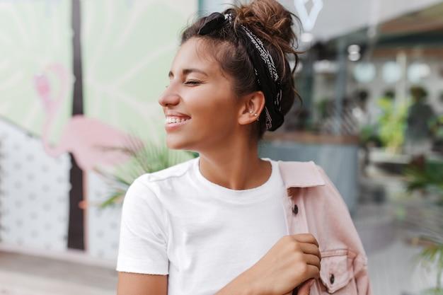 Close-upportret van gebruinde donkerharige vrouw met stijlvol broodje, glimlachend tegen muur van bar met geschilderde flamingo's Gratis Foto