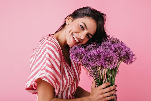 Close-upportret van gebruinde vrouw met charmante kuiltjes op haar wangen. meisje lacht schattig, haar hoofd kantelen naar bloemen. Gratis Foto