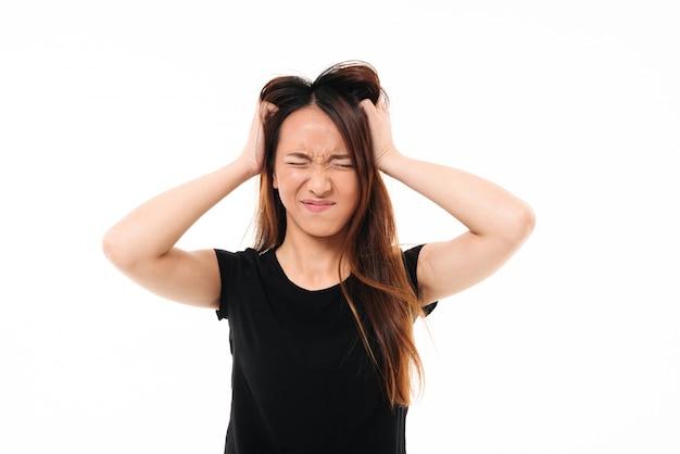 Close-upportret van geërgerde aziatische vrouw die met gesloten ogen haar hoofd houdt Gratis Foto