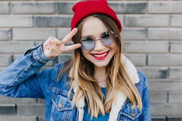 Close-upportret van glimlachend prachtig meisje dat van goede dag in het voorjaar geniet. buiten schot van spectaculaire dame in casual kleding poseren met plezier op bakstenen muur. Gratis Foto