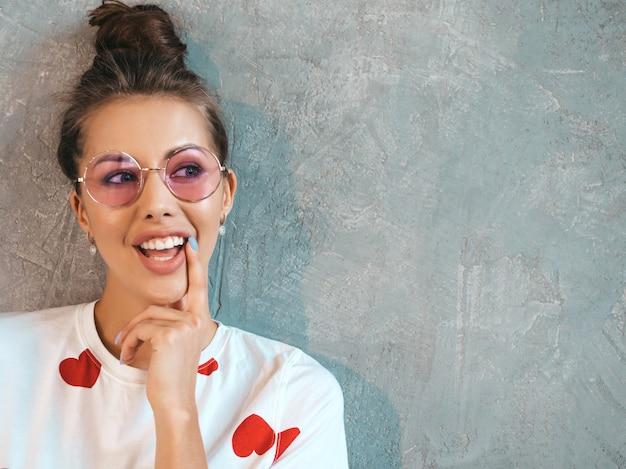 Close-upportret van het jonge mooie glimlachende vrouw kijken. trendy meisje in casual witte zomerjurk en zonnebril. . denken Gratis Foto