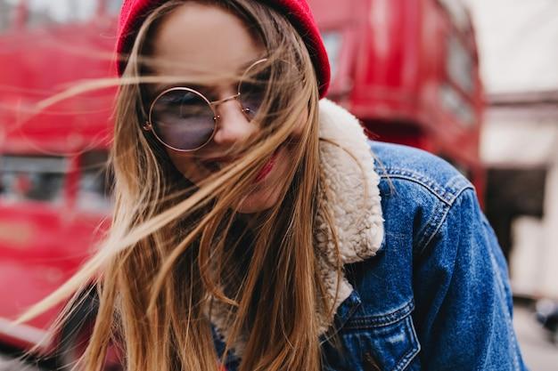 Close-upportret van innemende blanke vrouw met plezier in goede lentedag. betoverend kaukasisch meisje in stijlvol denim jasje lachen in de buurt van rode bus. Gratis Foto