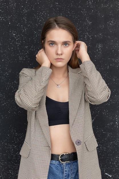 Close-upportret van jonge kaukasische vrouw met lang haar die zwarte bovenkant, jeans en kostuumjasje dragen bij studio. mooie dame poseren Premium Foto
