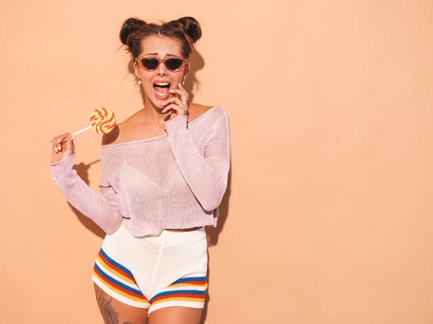Close-upportret van jonge mooie sexy glimlachende vrouw met lijkenetende kapsel. trendy meisje in casual zomer wit zwempak in zonnebril. heet model geïsoleerd op beige. eten, bijten snoep lolly Gratis Foto