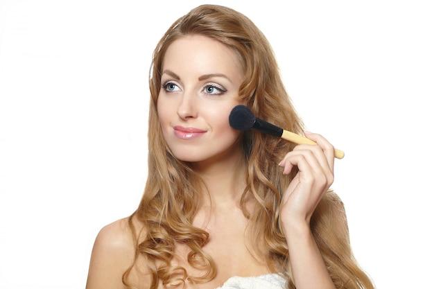 Close-upportret van jonge mooie vrouw die make-up toepast Gratis Foto