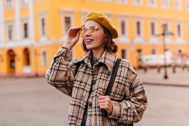 Close-upportret van jonge vrouw die in zonnebril stadsgezicht bewonderen Gratis Foto
