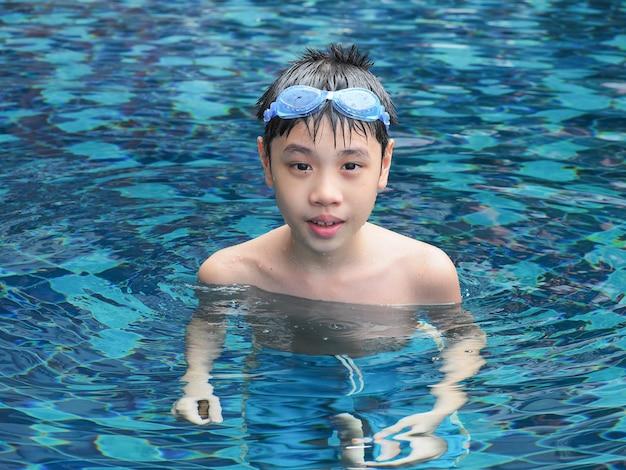 Close-upportret van leuke jongen in het zwembad Premium Foto