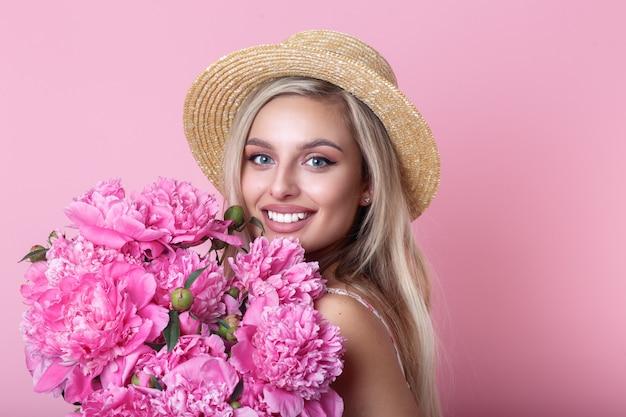 Close-upportret van mooie jonge vrouw in het boeket van de holdingspioenen van de strohoed over roze Premium Foto