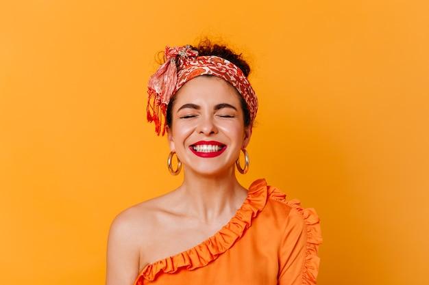 Close-upportret van positieve vrouw met rode lippen gekleed in blouse met blote schouder en hoofdband die met gesloten ogen op geïsoleerde ruimte lachen. Gratis Foto