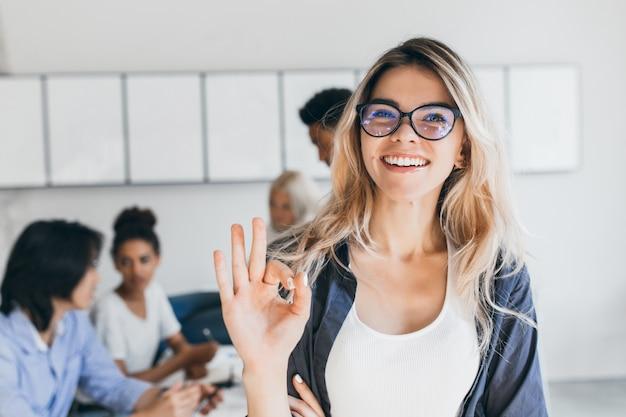 Close-upportret van vrij vrouwelijke manager van verkoopafdeling. indoor foto van lachende vrouw werkzaam in kantoor met mensen te bespreken. Gratis Foto