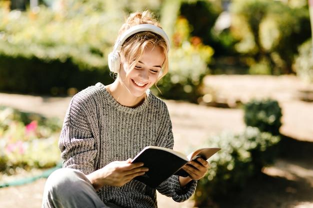 Close-upportret van vrouw die aan muziek luistert en een boek leest Gratis Foto