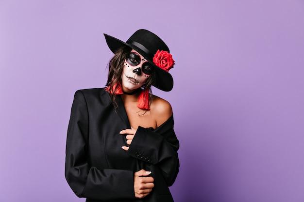 Close-upportret van vrouw met gepassioneerde blik. model in zwarte hoed met roos poseren op lila muur. Gratis Foto