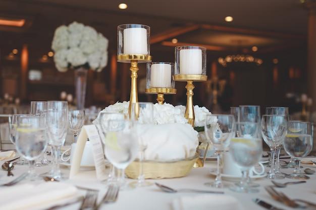 Close-upschot van witte pijlerkaarsen in kandelabers op een huwelijkslijst Gratis Foto