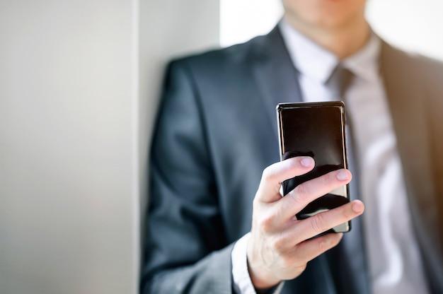 Close-upschot van zakenman die smartphone gebruiken op kantoor Premium Foto
